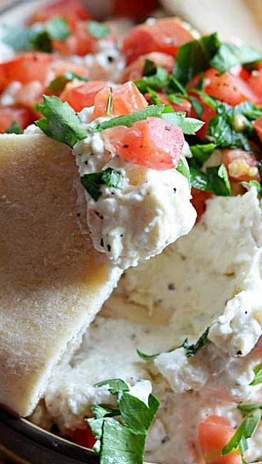 Garlicky Feta Dip6 oz feta cheese, crumbled 4 oz cream cheese, softened ⅓ cup greek yogurt 2-3 cloves garlic, minced Pinch of dried dill Pinch of dried oregano 1 tablespoon lemon juice 1 Roma tomato, diced Chopped parsley, to garnish Black pepper, to taste Pita, chips, or crackers, to serve