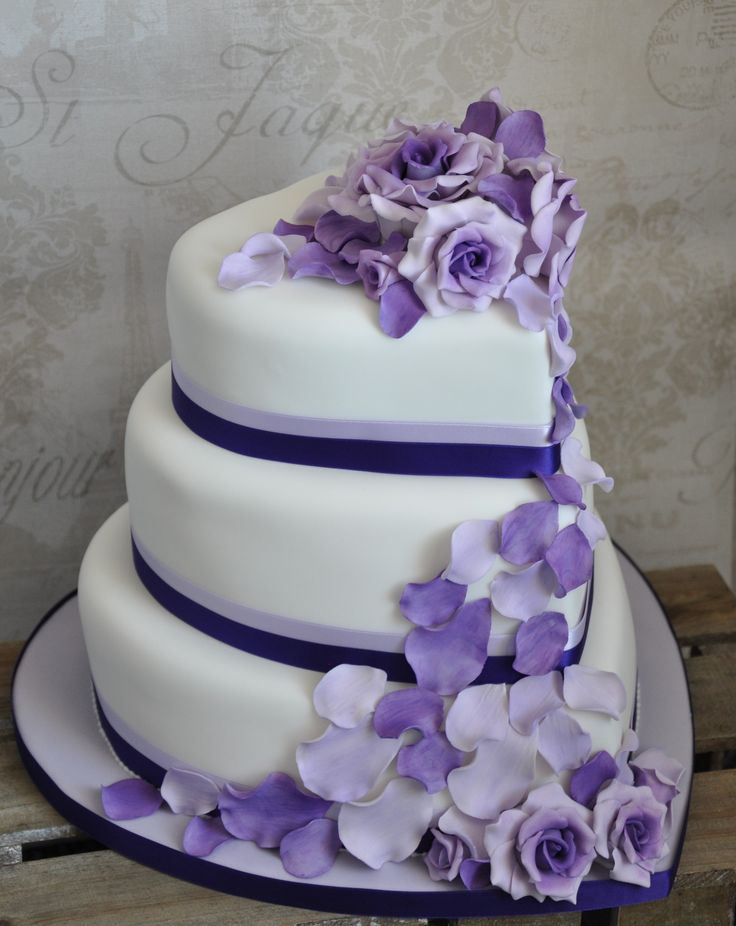 Three Tiered Heart Shaped Wedding Cake With Cascading Roses And Petals In Shades Of Purple