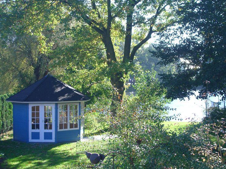 Elegant Gartenpavillon in leuchtendem Blau traumhaft an einem See gelegen