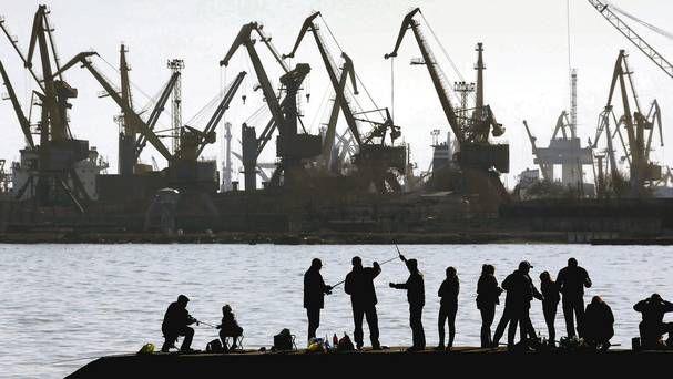 People fish on a pier at the port of Mariupol, eastern Ukraine (Reuters, Yannis Behrakis)