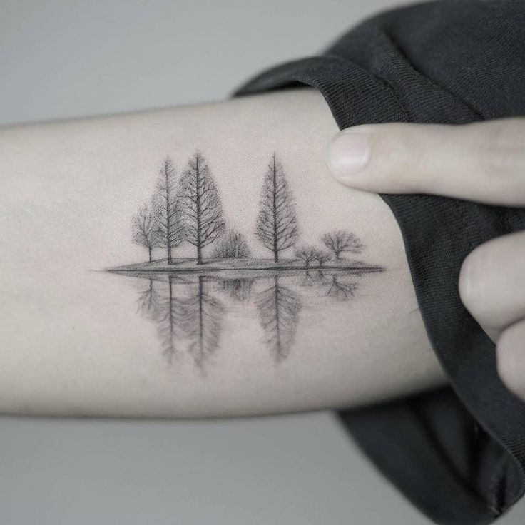 A quiet lake in winter tattoo on the right arm.