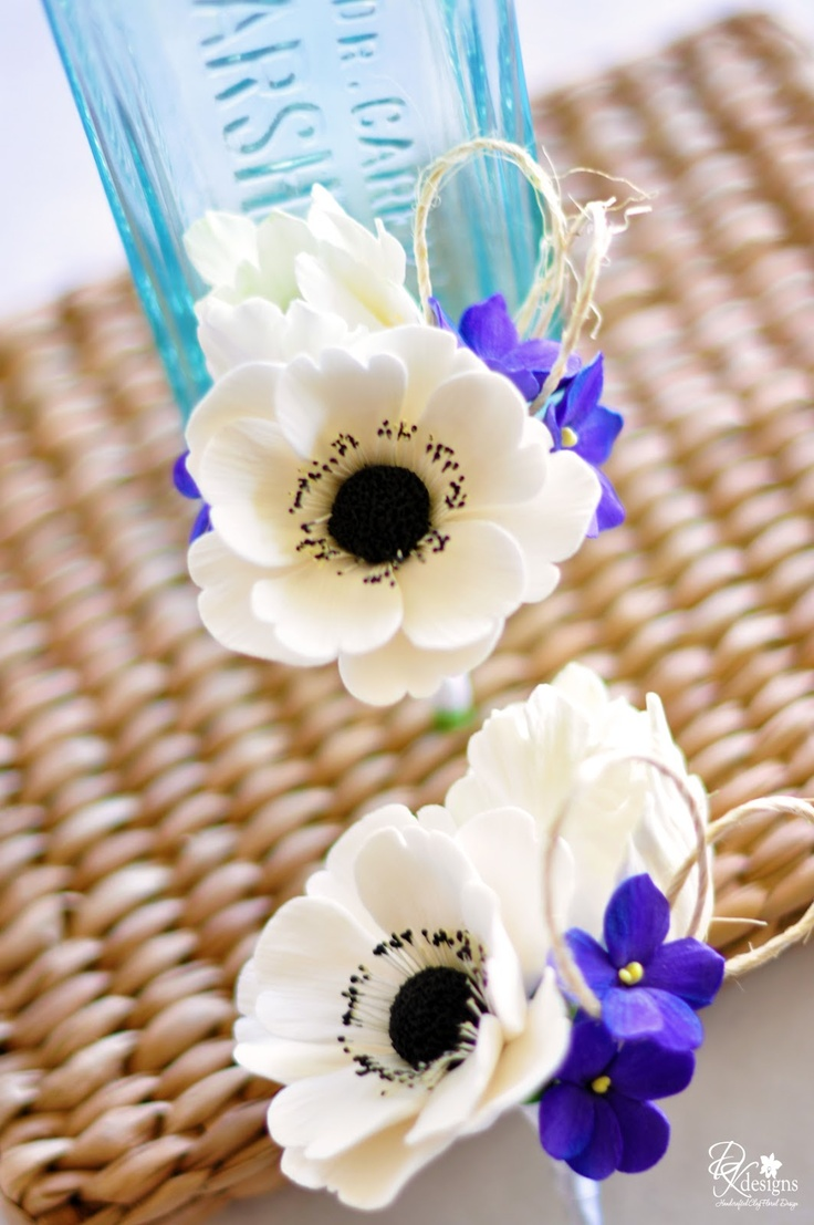 DK Designs - corsages with white anemones, white tulips and purple violets with twine accents.