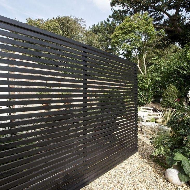 A slatted fence made of western cedar primed trim board by Silva Timber. For more see Trend Alert: Black Fences. ; Gardenista