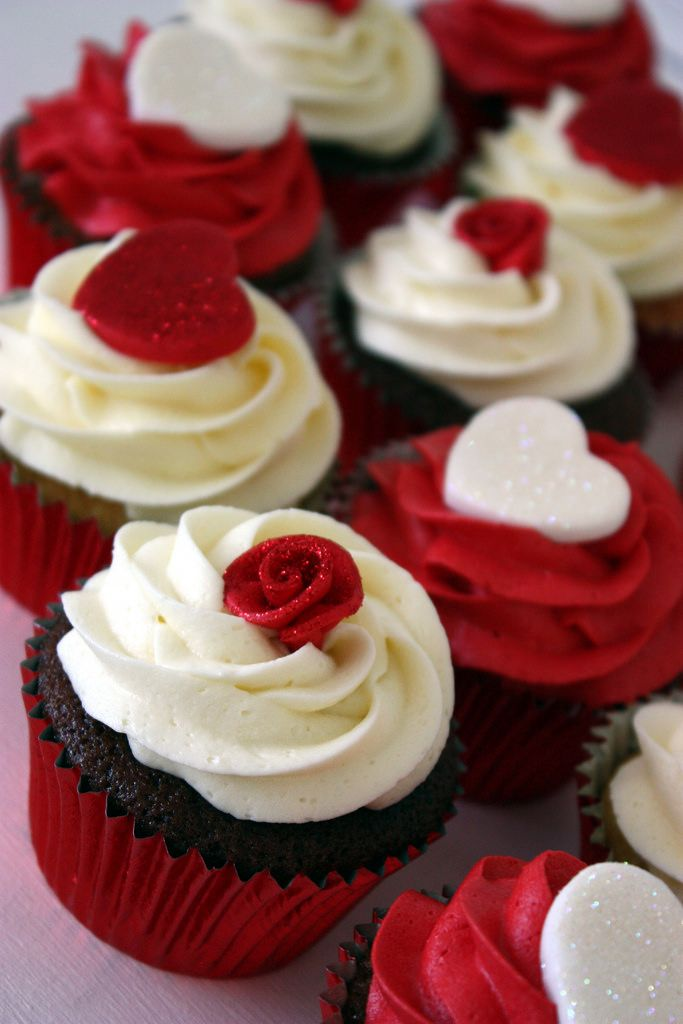 Ivory and red glittery hearts and ribbon roses topped these wedding cupcakes.  The cutting cake was Traditional Rich Fruitcake, with a heart shaped cookie topper (I made a similar one in the past which the bride loved).  Flavours were:  Carrot Cupcakes with Orange Buttercream White Chocolate Cupcakes with White Chocolate Buttercream Chocolate Cupcakes with Coconut Buttercream  Unfortunately I didn't set this wedding up at the venue so these are quick snapshots before I boxed them up for t...