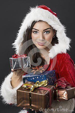 Beautiful young woman dressed in Santa costume carrying bunch of wrapped Christmas presents over dark background.