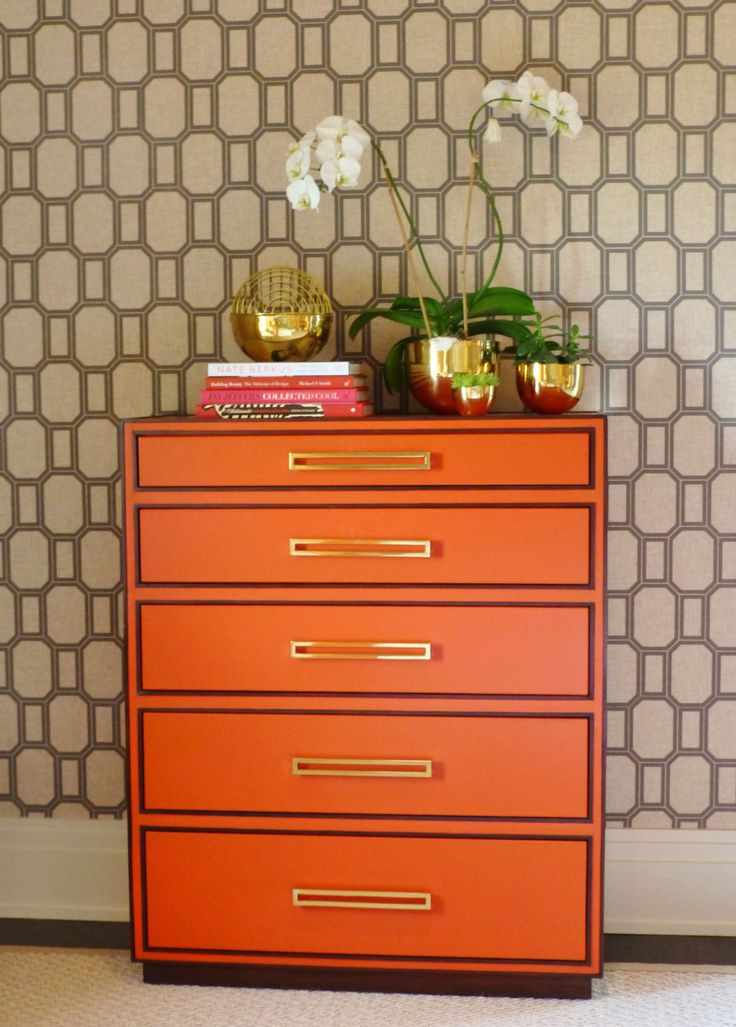 On the opposite side of the bed is this stunning orange chest of drawers.  The color brings to mind the iconic Hermes branding. And don't you just love the wide brass drawer pulls?  The look amazing with the brass accessories atop the bureau, which have a funky 1970's vibe.
