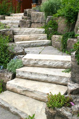 Stone for front yard.   Owen Sound natural stone slab steps and landings; armour boulders with planted gardens.