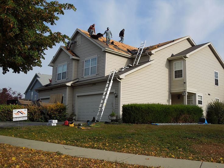 Employees standing on a roof and repairing old construction after wind damage