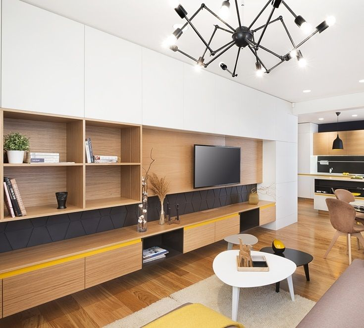 Your apartment's small living room design is so crucial in defining your overall home design. In this example, we see the use of wood in a few different areas of the home. The hardwood floors are the same stain as the living rooms and kitchen cupboards. By using the same stain, the room appears larger and sleek.