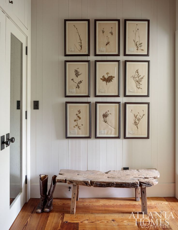 A series of botanicals from Holland & Company hang above a bench from B.D. Jeffries