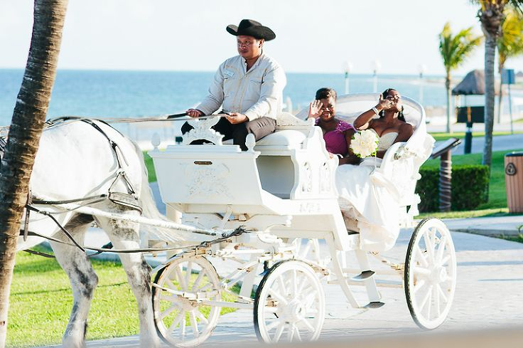 Bride Kim and her mother arrive at the destination wedding ceremony in a white horse drawn carriage #FairytaleWedding | Moon Palace Cancun