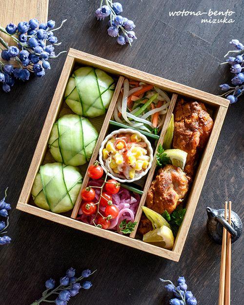 Bento box featuring onigiri spheres wrapped in cucumber, imitation crab and corn mayo salad, and karaage