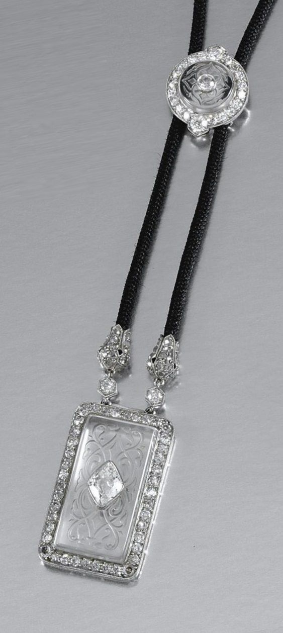 CARTIER - A BELLE EPOQUE ROCK CRYSTAL AND DIAMOND SAUTOIR, CIRCA 1910. Suspending a rectangular rock crystal plaque carved with foliate motifs, inset to the centre with a lozenge-shaped diamond, to a border millegrain-set with circular- and single-cut stones, mounted on a cord with an annular slider similarly set, signed Cartier Londres and numbered. #Cartier #BelleÉpoque