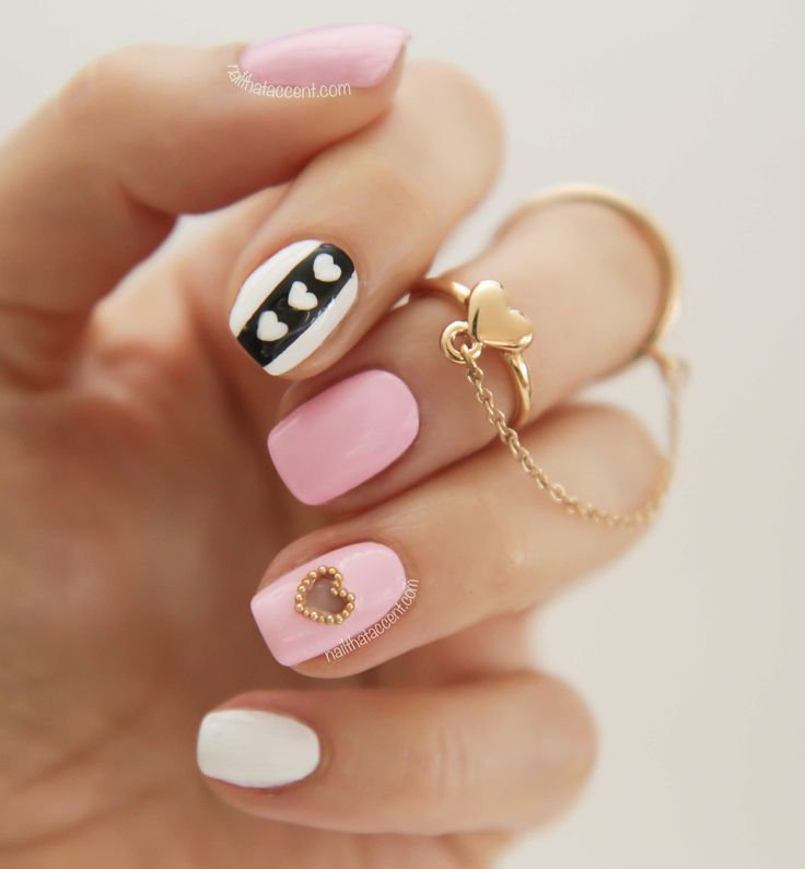 Cute Valentine's Day manicure with pastel pink, black & white polishes, hand painted mini hearts & even a gold bead outlined negative space heart! Talk about a detailed nail design. ♥
