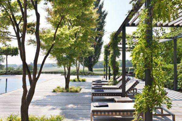 trädäck med integrerad grönska, träd ger höjd och vandrande skugga, rumskänsla med stolpar och pergolatak, klätterväxter, dosen grönska rätt till trädäcket storlek