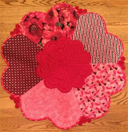 "Love is All Around Table Mat Pattern by Quilted Garden at KayeWood.com. 31"" diameter. Pieced hearts with a little applique, yoyo's and bias binding all come together to make this sweet topper. http://www.kayewood.com/item/Love_is_All_Around_Table_Topper_Pattern/3766 $11.00"