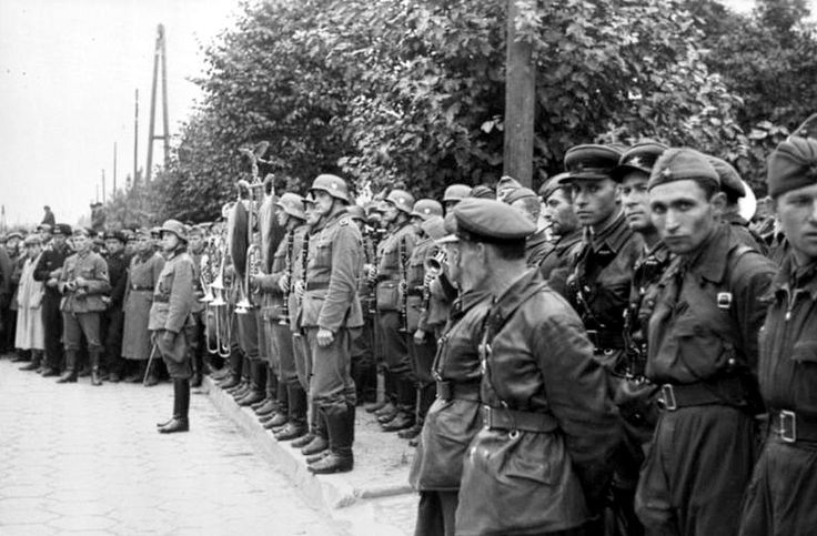 "Side by side, German and Soviet troops watch their joint victory parade in the streets of Brześć Litewski during the partitioning of Poland. The German invasion of Poland began on 1 September 1939 and the Soviet invasion of Poland began on 17 September 1939 after the two countries signed the Molotov-Ribbentrop Pact. The treaty was a mutual non-aggression pact and included a secret protocol that divided Poland, Lithuania, Latvia, Estonia, Finland and Romania into German and Soviet ""spheres…"