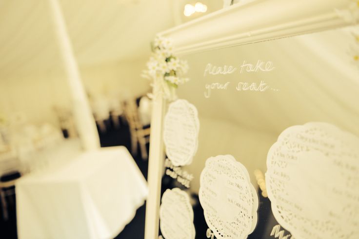 DIY wedding table plan mirror - hand painted mirror in white, glued on fake flowers in the corners, used chalk pen, doilies and printed names to show people where they were sitting!