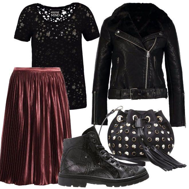 Un look rock composto da una giacca di pelle abbinata alla gonna plissè, t-shirt a manica corta trasparente, stivaletto nero e infine come accessorio una borsetta a secchiello con borchie.