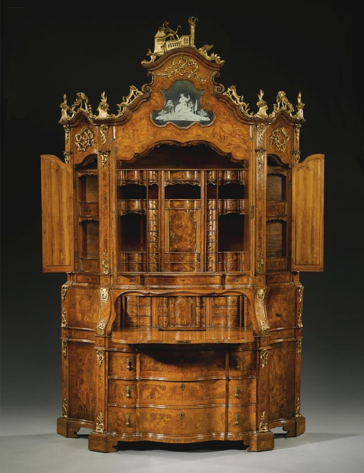 An Italian walnut, burr walnut and parcel-gilt bureau cabinet, Venetian mid 18th century the upper section with an arched top surmounted by a pierced balustrade with a peacock  flanked by a tree, column and a stylised building surmounted by a pierced scroll, rocaille, flower and foliate carved cresting above a cartouche-shaped engraved mirror depicting a seated female in 18th century dress in a landscape representing Juno above a pair of mirrored doors opening to reveal a fitted interior
