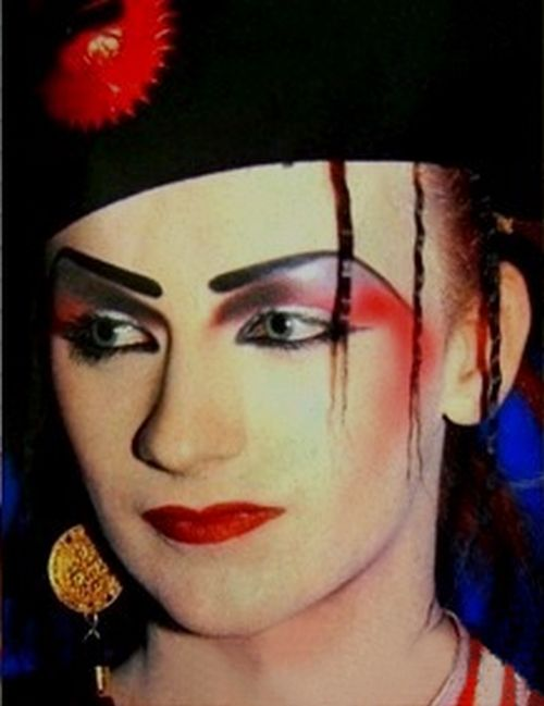 [Boy George with impeccable eyebrows and red and black eyeshadow]