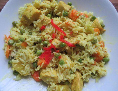 Für Hühnercurry mit Ananas und Reis die Hühnerbrust in mundgerechte Stücke schneiden und in einer Pfanne mit Ghee anbraten. Currypulver,
