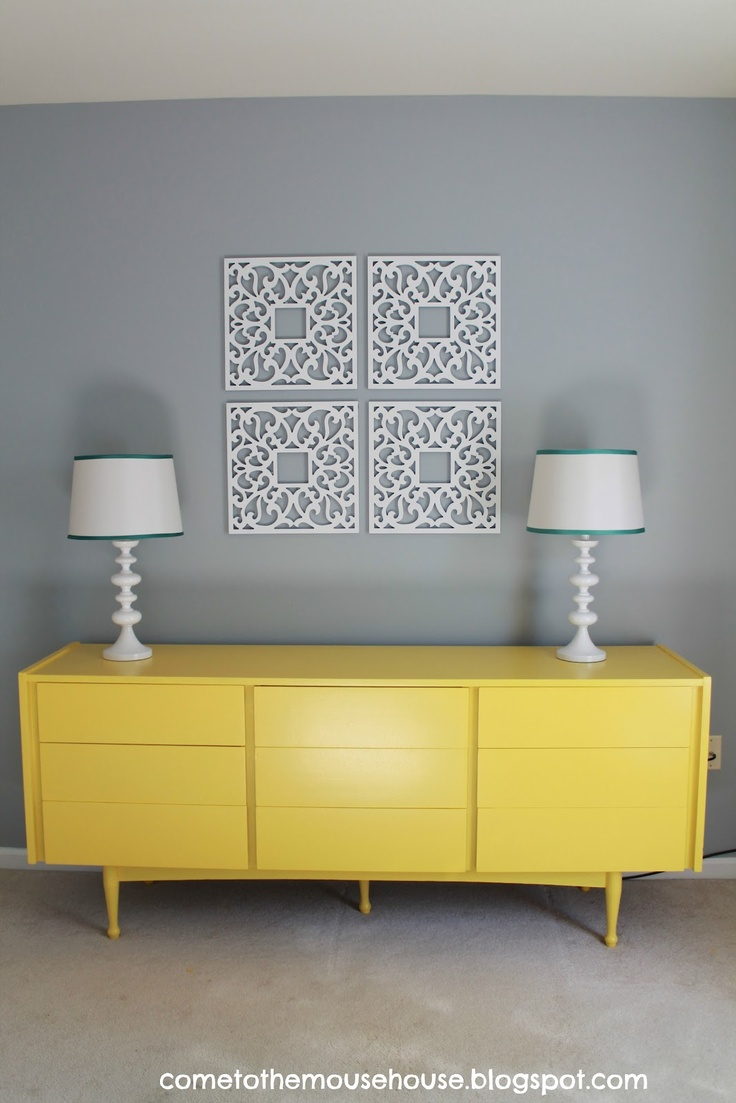 Yellow mid-century modern triple dresser.  Cleverly used in a playroom to store toys.