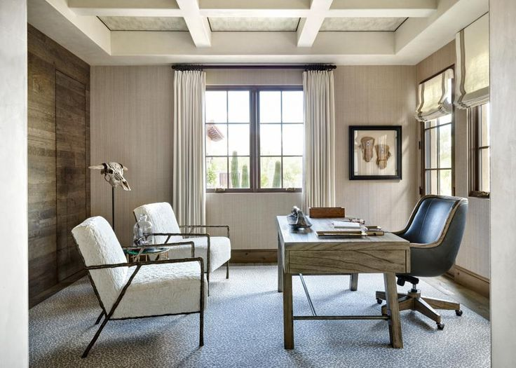 A sleek wooden desk is paired with a comfy leather chair in this contemporary, southwestern home office. Upholstered fur chairs features a streamlined metal frame, while the speckled area rug brings in lots of visual texture.