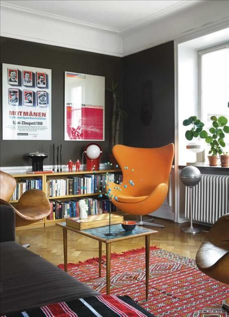 """charcoal with a touch of the darkest olive green + orange and red. says apartment therapy: """"A typical dark, low ceilinged...apartment will look infinitely more chic and cheerful painted something dramatic, like charcoal gray...It's counter-intuitive, but it lends a blah space a strong presence. You can always lighten the mood with bright accent pieces and good lighting."""""""