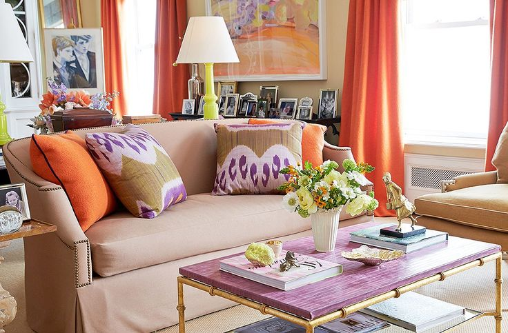 """Brilliant colors lead the way in the ever-changing living room (""""It's a hazard of the profession""""), starting with the punchyorange boiled wool by Holland & Sherry used on the curtains and pillows and the purple leather-top table designed by Amanda for Niermann Weeks."""