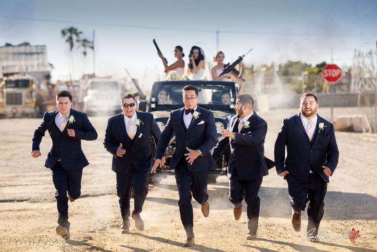Super fun Bridal Party picture! Bride and Bridesmaids chasing down the Groom and Groomsmen in a Jeep Wrangler with guns