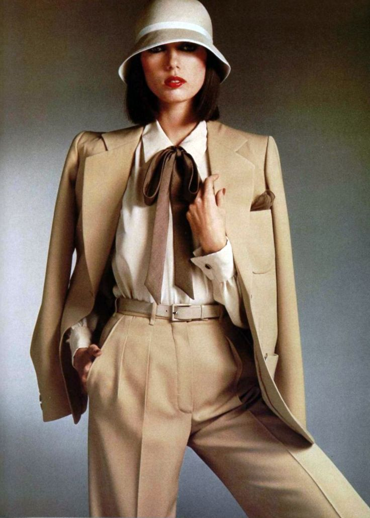 Yves Saint Laurent - L'Officiel magazine 1976 vintage fashion style pantsuit pants jacket suit tan brown tweed wool gaberdine blouse bow tie hat belt 70s designer model magazine print ad color