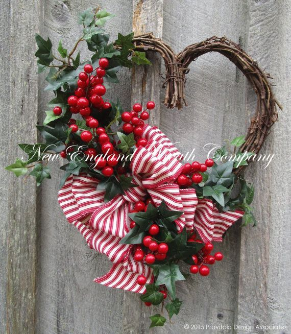 Sweetheart Berry Wreath. Bright cherry red berry clusters and and lush English Ivy line the edge of a rustic grapevine heart frame. A lush 6-loop bow in a striking red and white ticking stripe adds a