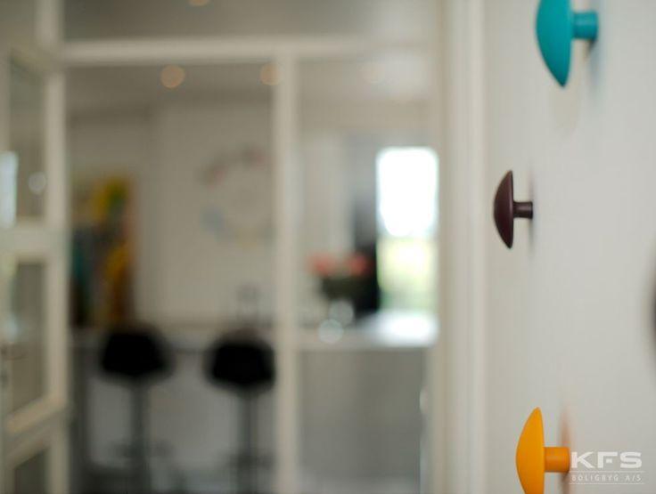 Hos KFS Boligbyg danner vi fundamentet for din bolig, med det er dine egne personlige detaljer, der fuldender drømmen. Farverige knager i gangen, er med til at udtrykke din stil.