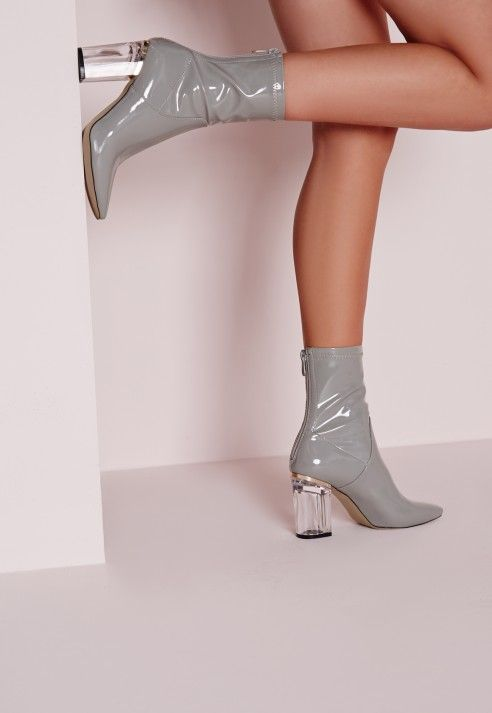 Ensure all eyes are on you with this seasons hottest heeled ankle boots! Featuring a clear block heel, zip to the back and shiny patent finish in a light grey shade, these boots are one fierce pair. Team up with your favourite mini skirt fo...