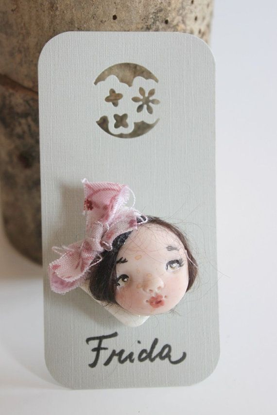 This listing is for Frida doll face brooch you can see in picture 1. She's handmade in polymer clay and wool. This brooch is one of a kind.  Other faces are available as on pictures 2/3/4