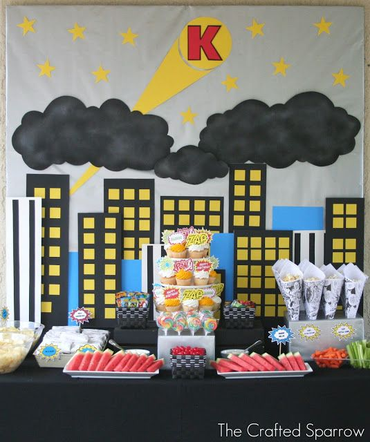 Cute super hero baby shower table set up with the baby's initial in the signal