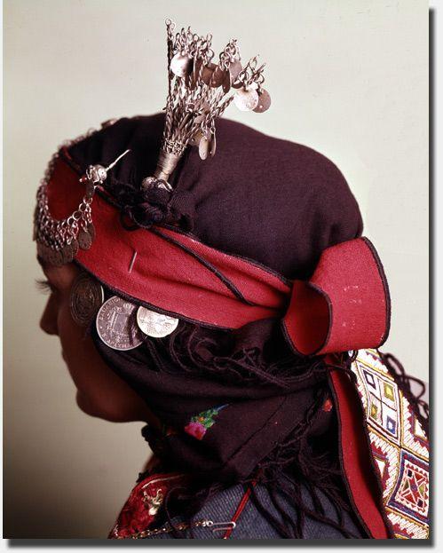 """Το σουργούτ (στολίδι στον κεφαλόδεσμο της γυναικείας φορεσιάς των Καπουτζήδων Θεσσαλονίκης) λειτουργούν ως ρυθμικό μουσικό όργανο, συνοδεύοντας το βάδισμα και τον χορό με τον λεπτό «ασημένιο» τους ήχο. / The sourgout (ornament to the headband female costume of Kapoutzides Thessaloniki) operating as a rhythmic instrument, accompanying walking and dancing to the minute """"silver"""" sound."""
