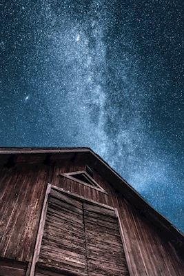 Starry night with visible Milkyway above a wodden barn in Småland, Sweden. Photographer Johan Spjuth, available as poster at printler.com, the marketplace for photo art.
