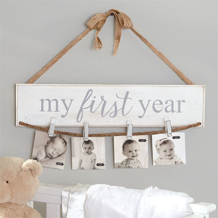 Painted mango wood photo holder features printed 'My First Year' sentiment and jute cord with four wood clothespins for hanging photos, cards or memorabilia. Arrives with jute ribbon and bow to hang on wall.