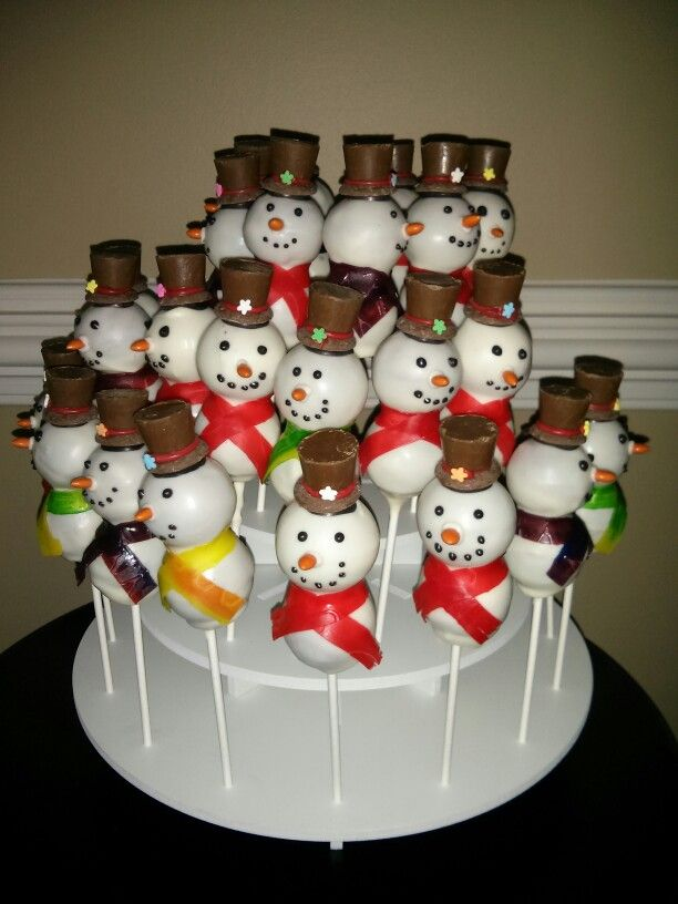 Snowman Cakepops- Rollos, candy coating (light cocoa, red, white, and black), flower sprinkle, chocolate covered sunflower for the nose and fruit by the roll.