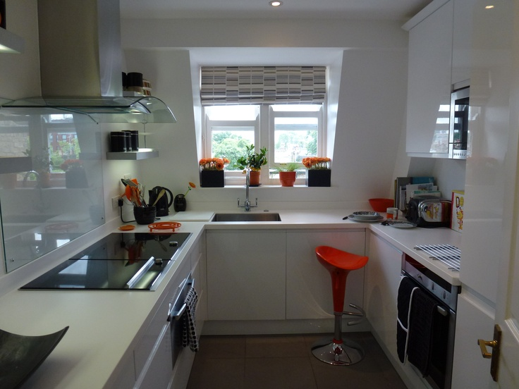 White Kitchen Orange Accents a minimal all-white gloss kitchen with orange accent accessories