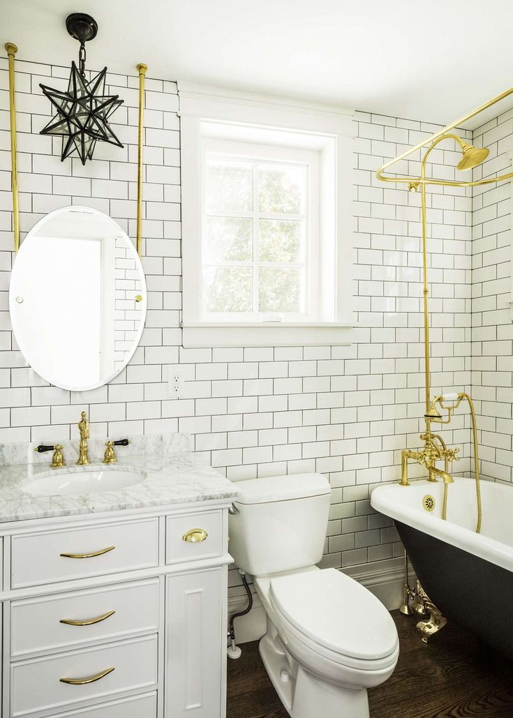 Classic and traditional style in a bathroom with walls of subway tile. Moravian star pendant, round mirror, clawfoot tub painted black, and bright brass accents.Design by The Fox Group. #bathroomdesign #timelessbathroom #bathroomdecor #subwaytile #brasshardware #blackandwhite #interiordesign