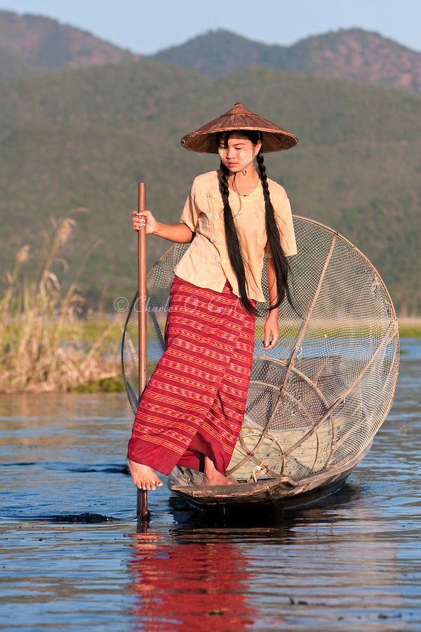 Myanmar, Burma.  Young Burmese Woman Rowing with one Leg, Looking for a Place to Set her Fishing Net.  Inle Lake, Shan State.  She is wearing thanaka paste on her cheeks, a Burmese cosmetic sunscreen. Cecil Images