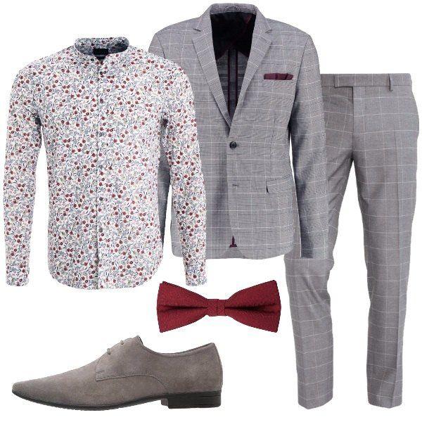 Outfit formato da un completo di giacca e pantaloni grigio a quadretti. La camicia è a fantasia. spiritosa ma anche elegante nell'insieme. Il look si completa grazie alla scarpa stringata grigia e al papillon bordeaux. Un total look pensato per un invito speciale.