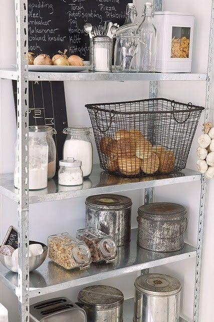 Ejemplo acerca de cómo la típica y por de más económica estantería metálica de oficina puede lucir magnífica en la cocina. En este caso, se mantuvo la paleta neutra, haciendo mucho uso del metálico, lo que da un estilo industrial.