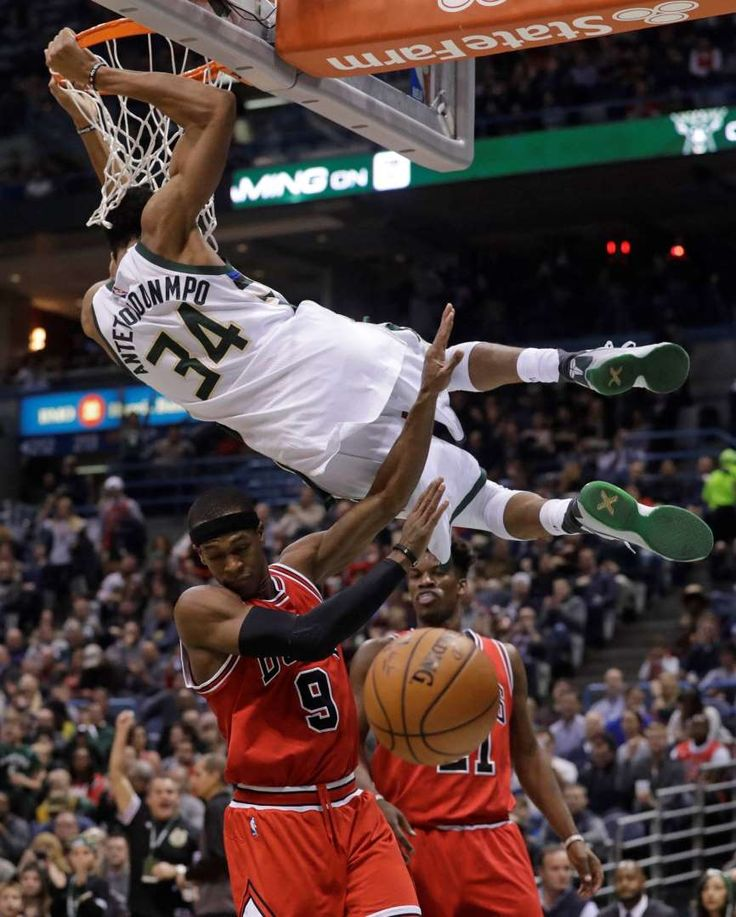 Milwaukee Bucks' Giannis Antetokounmpo dunks over Chicago Bulls' Rajon Rondo and Jimmy Butler during... - Morry Gash/AP Photo