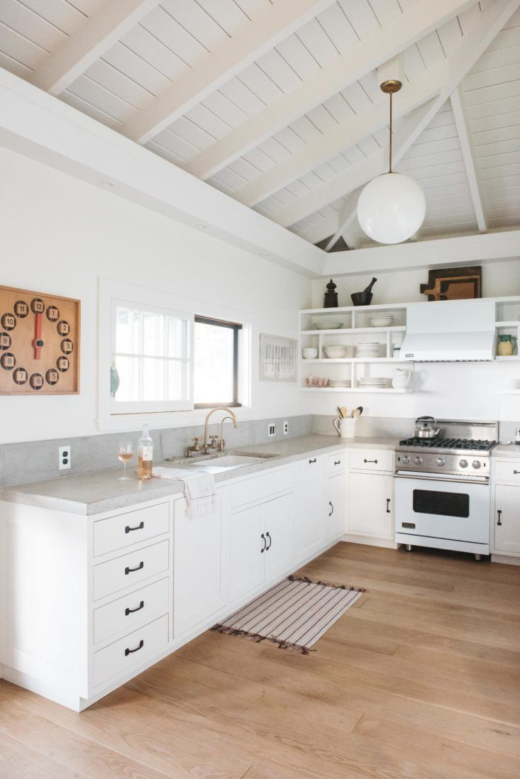 white dove by Benjamin Moore, white rafters over large white kitchen with wooden floors, small rug, grey worktops, white open shelves, white globe light