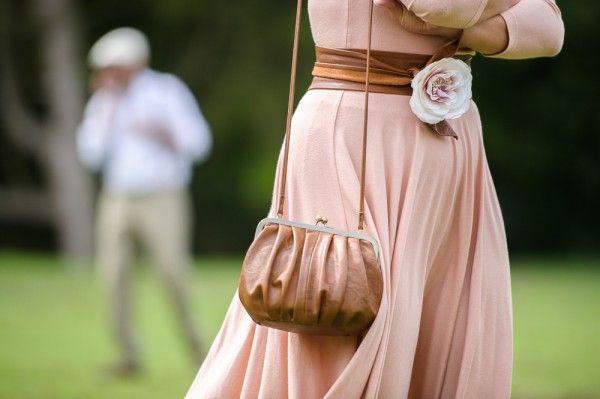 Une robe rose, un sac camel, une fleur. C'est doux et romantique.