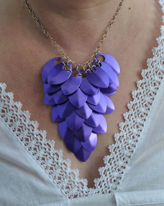 A beautiful statement piece of scale maille jewellery. Made from purple aluminium scales, linked with jump rings. Each scale measures 35 x 22 mm. The pattern is hung from silver plated chain and finished with a silver plated toggle clasp. The scale pattern measures approx 10 cm x 11.5 cm. The scales are attached to a 41cm (16 inch) length of chain. A made to order item. Will arrive to you gift boxed. Perfect wedding jewellery, for bridesmaids or brides. Also beautiful teamed with a black…